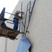 Man Working on Installing Laminate Sign at Kilgore College