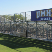 UMHB Wayfinding Large sign attached to fencing behind stadium bleachers