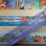 Pomeroy Elementary School wall mural beside staircase featuring bright vivid cultural graphics