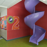 Pomeroy Elementary School Wall panels near spiral purple slide featuring bright vivid cultural graphics