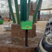 Small interpretive sign on pedestal in payground with large snail sculpture
